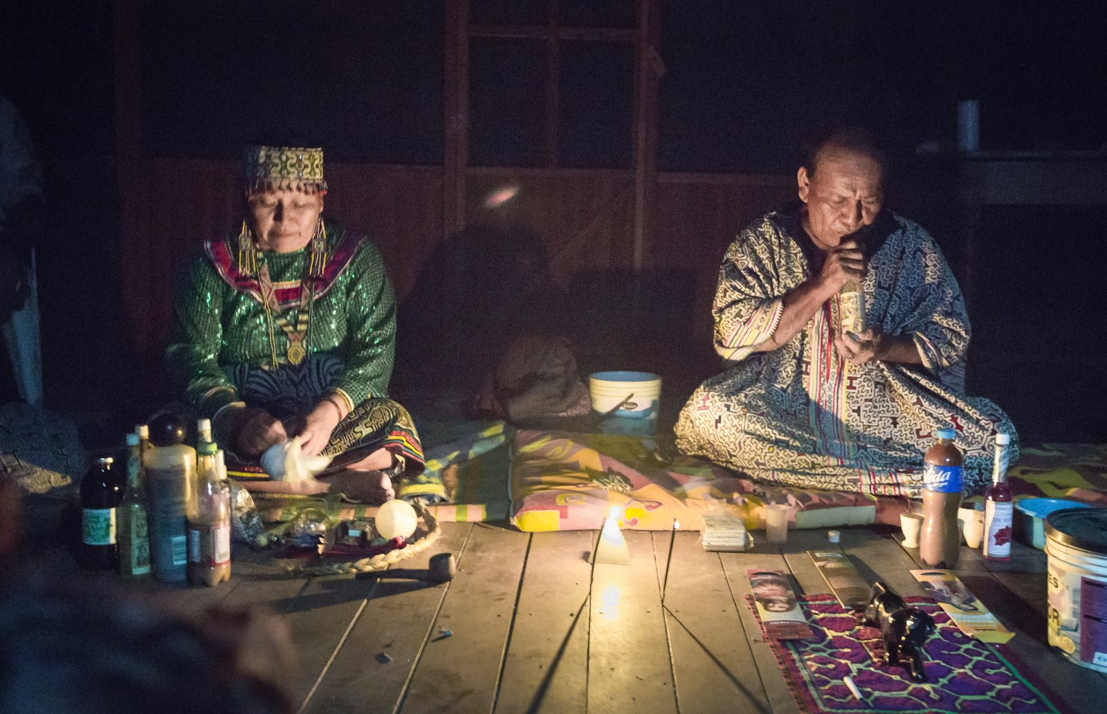 "Host parents, Magda and Enrique, prepare for an ayahuasca ceremony. The muddy liquid stored in a reused plastic soft drink bottle is the psychedelic plant brew. The ceremony will last five hours, and Magda and Enrique will guide participants through song or ""icaros."""