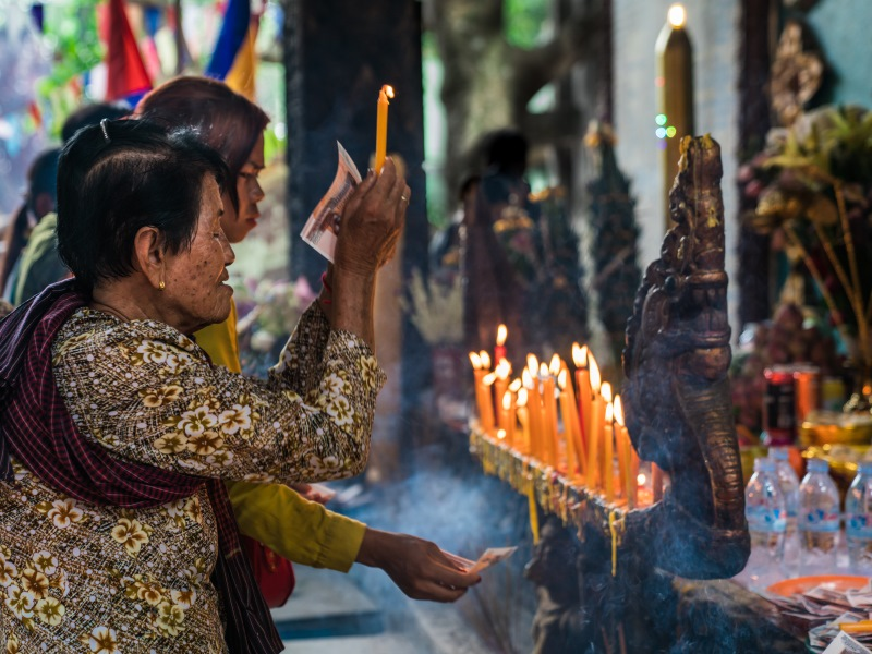 Cambodian woman at local temple lights a candle during prayer.
