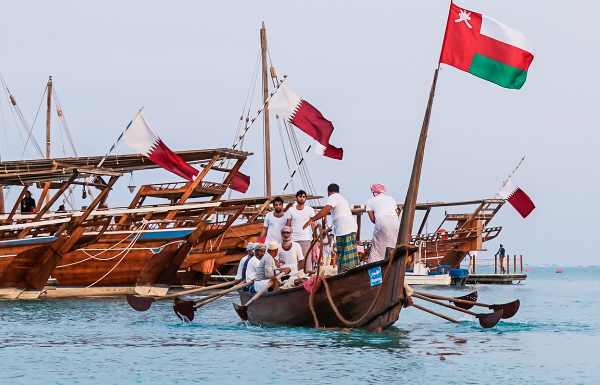 Qatari and Omani flags are proudly displayed together on a traditional dhow boat as the men unite and deploy their fishing nets in the Persian Gulf.