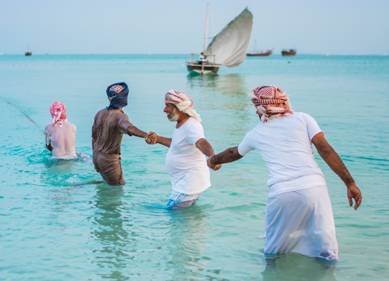 Men from Oman and Saudi Arabia demonstrate camaraderie as the Middle Eastern neighbors join hands to use their united power and strength to draw the fishing nets closer.