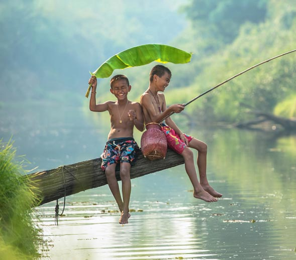 Two kids fishing on a log and smiling
