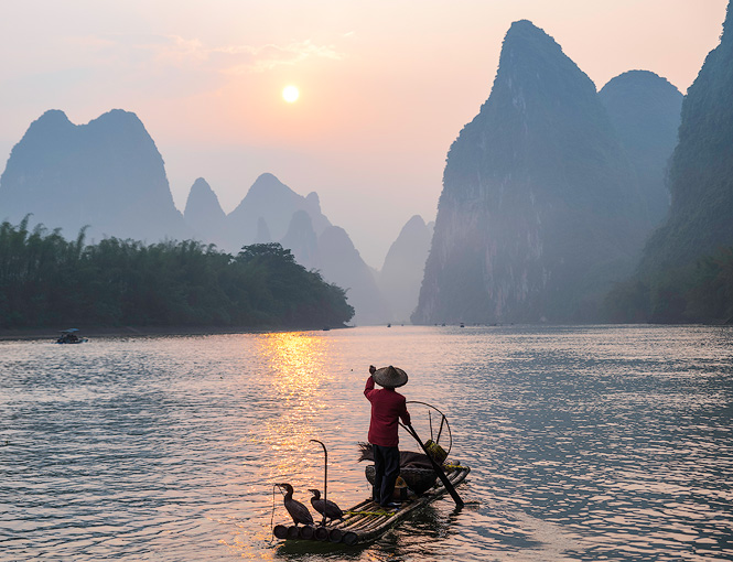 A Chinese fisherman with his Cormorant birds paddle off on the Li River in Xingping, China.